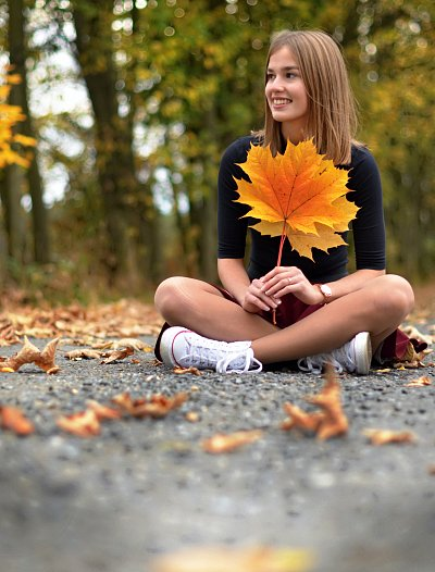 a girl dressed into yellow maple leaves